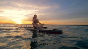 Una mujer descansa sobre su paddleboard en el océano, meditando 4K metrajes