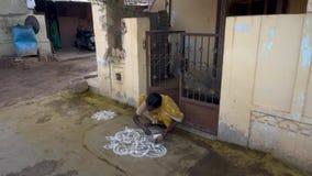 Una mujer dibuja un dibujo del rezo en la tierra almacen de metraje de vídeo