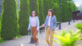 Una mujer discapacitada joven con lesión en las muletas va con un amigo y una charla MES lento sonriente metrajes