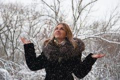 Una mujer disfruta en la nieve que cae El caminar en el parque en la nieve Fotos de archivo