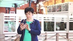 Una mujer durante 40 años de edad disfruta de los paisajes urbanos del smartphone almacen de metraje de vídeo