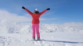 Una mujer elegante del esquiador en la montaña máxima, manos de los aumentos para arriba imagenes de archivo