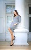 Una mujer elegante en el fondo de una casa blanca grande La señora hermosa en un vestido gris y zapatos negros al aire libre fotos de archivo libres de regalías