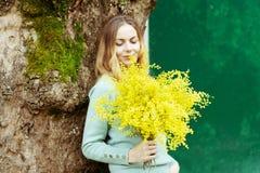 Una mujer elegante joven es sonrisa, celebrando un presente en su mano un ramo de flores frescas de la mimosa imagen de archivo libre de regalías