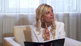 Una mujer elegante piensa y escribe algo en su cuaderno almacen de video