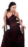 Una mujer elegante vestida en un vestido rojo oscuro se sienta en una silla Imagen de archivo
