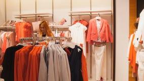 Una mujer elige un traje en una tienda de ropa del ` s de las mujeres Imágenes de archivo libres de regalías