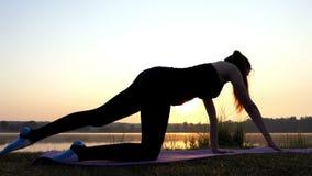 Una mujer embarazada aumenta su brazo y pierna en una estera en un banco del lago en la puesta del sol almacen de video