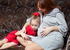 Una mujer embarazada con su hija en el sofá Foto de archivo