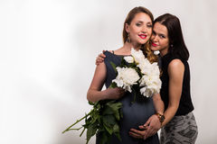 Una mujer embarazada con una novia en un fondo ligero Fotos de archivo