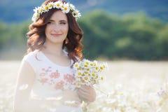 Una mujer embarazada en un campo con un ramo de margaritas blancas Fotografía de archivo libre de regalías
