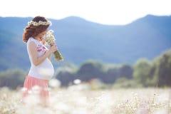 Una mujer embarazada en un campo con un ramo de margaritas blancas Imagen de archivo