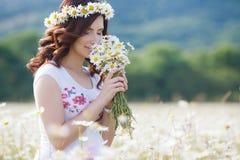Una mujer embarazada en un campo con un ramo de margaritas blancas Fotos de archivo libres de regalías