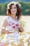 Una mujer embarazada en un campo con un ramo de margaritas blancas Foto de archivo libre de regalías