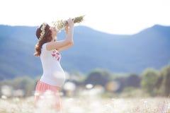 Una mujer embarazada en un campo con un ramo de margaritas blancas Fotografía de archivo