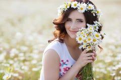 Una mujer embarazada en un campo con un ramo de margaritas blancas Imágenes de archivo libres de regalías