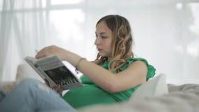 Una mujer embarazada en una blusa verde que se sienta en el sofá y que lee un libro almacen de video
