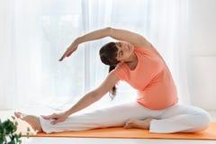 Una mujer embarazada europea con la camiseta rosada hace los ejercicios de la yoga para el carehealth su y el niño nonato en dorm Imagenes de archivo