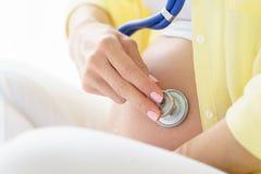 Una mujer embarazada europea con sonrisa es golpe de corazón que escucha del niño nonato dentro de su panza al lado de estetoscop Fotos de archivo