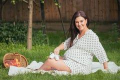 Una mujer embarazada feliz joven goza de los zapatos del bebé futuro imagenes de archivo