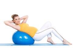 Una mujer embarazada hace la gimnasia con la bola Imagen de archivo