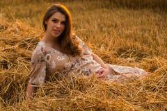 Una mujer embarazada joven entre el campo de trigo Fotos de archivo