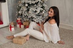 Una mujer embarazada que se sienta por el árbol de navidad abre regalos de Navidad fotos de archivo libres de regalías