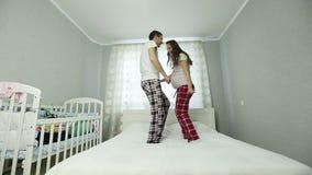 Una mujer embarazada y un hombre en los pijamas que bailan en la cama almacen de video