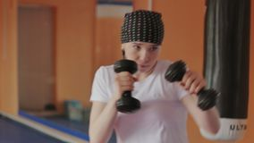 Una mujer enérgica en el boxeo en el gimnasio, coches en pesas de gimnasia metrajes