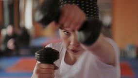 Una mujer enérgica en el boxeo en el gimnasio, coches en pesas de gimnasia almacen de metraje de vídeo