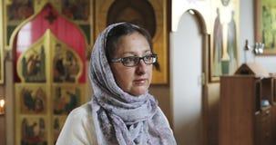Una mujer en una bufanda y vidrios está rogando en la iglesia almacen de video