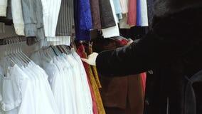 Una mujer en una capa de Muton elige un vestido en una tienda de ropa almacen de metraje de vídeo