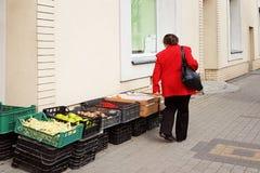 Una mujer en una capa roja elige las verduras presentadas en cajas en la entrada a un colmado en la calle Campos de la cosecha y  fotos de archivo libres de regalías