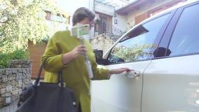 Una mujer en una capa verde, entra, consigue el coche almacen de video