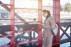 Una mujer en una capa y una mochila elegantes que lee un libro cerca de los estantes de madera rojos con los libros Foto de archivo