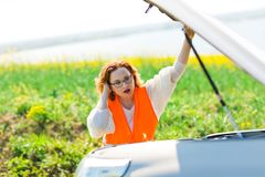 Una mujer en capo abierto del coche del chaleco anaranjado del coche quebrado imagen de archivo libre de regalías