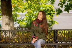 Una mujer en una chaqueta de la primavera en un banco en el parque Fotografía de archivo