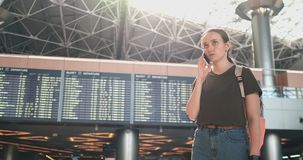 Una mujer en el aeropuerto en el teléfono que discute el retraso de su vuelo almacen de metraje de vídeo