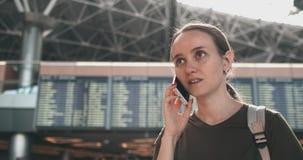 Una mujer en el aeropuerto en el tel?fono que discute el retraso de su vuelo metrajes