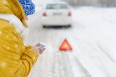 Una mujer en invierno llama a los servicios de emergencia Foto de archivo libre de regalías