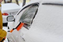 Una mujer en invierno quita nieve con el coche fotos de archivo libres de regalías