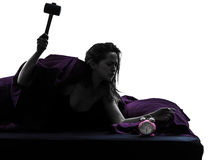 Mujer en la cama que despierta la silueta sensacional del despertador Foto de archivo