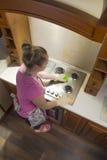 Una mujer en la cocina limpia una estufa de gas Fotos de archivo libres de regalías