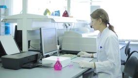 Una mujer en la investigación del laboratorio investigación en el laboratorio de investigación el científico de la mujer trabaja  metrajes