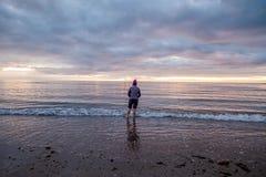 Una mujer en la playa en la salida del sol Imagen de archivo libre de regalías