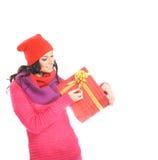 Una mujer en la ropa roja caliente que lleva a cabo un presente Fotografía de archivo