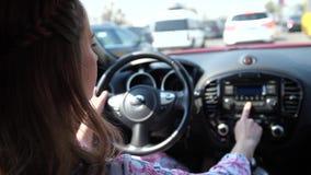 Una mujer en la rueda, en el atasco de tráfico por carretera, una mujer cambia la estación de radio 4K MES lento almacen de video