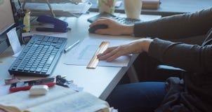 Una mujer en la tabla que trabaja en el ordenador fotos de archivo libres de regalías