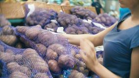 Una mujer en las verduras de compra de un supermercado, patatas almacen de metraje de vídeo