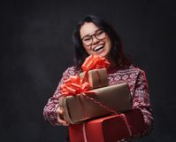 Una mujer en lentes sostiene los regalos de la Navidad imagen de archivo libre de regalías